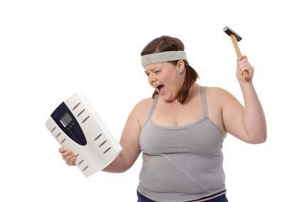 Overweight Woman Hitting Weight Scale WIth Hammer